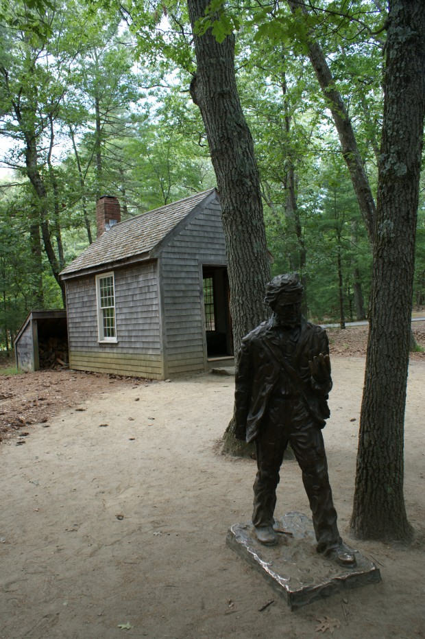 A statue of Thoreau stands outside a replica of the cabin where he lived and wrote for two years.